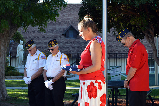 Max Lancaster/Boulder City Review Grace Christian Academy Principal Devon Tilman, center, bows her head in prayer, retired flag in hand, as members of American Legion, Post 31, and students and fa ...
