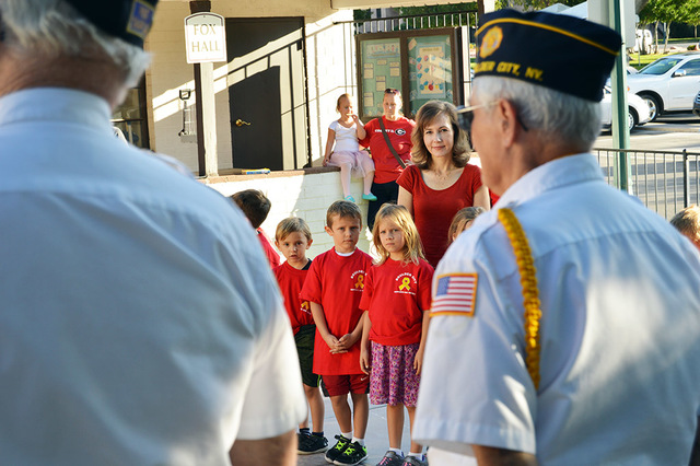 Max Lancaster/Boulder City Review Dylan Merrithew, 6, from left, TJ Bertoli, 6, and Eliza Ballit, 6, stand behind their first-grade teacher Anne-Marie Garner as members of American Legion, Post 31 ...