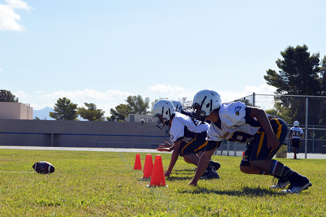 Freshman Nate Wilson, front, and other Boulder City High School defensive linemen practice waiting until the ball is snapped and pursuing the ball carrier. The linemen did jump before the ball was ...