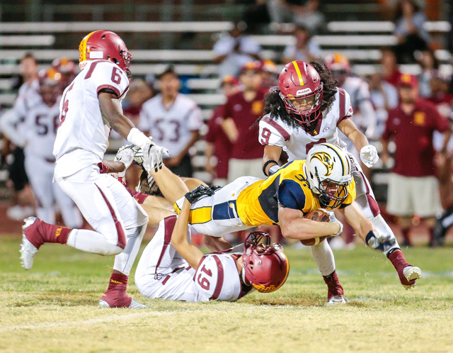 Donavon Lockett/Boulder City Review Boulder City High School sophomore Ryan Vannario reaches out as he is brought down by Del Sol Dragon Chevy Green, on the ground, during Friday's homecoming game ...