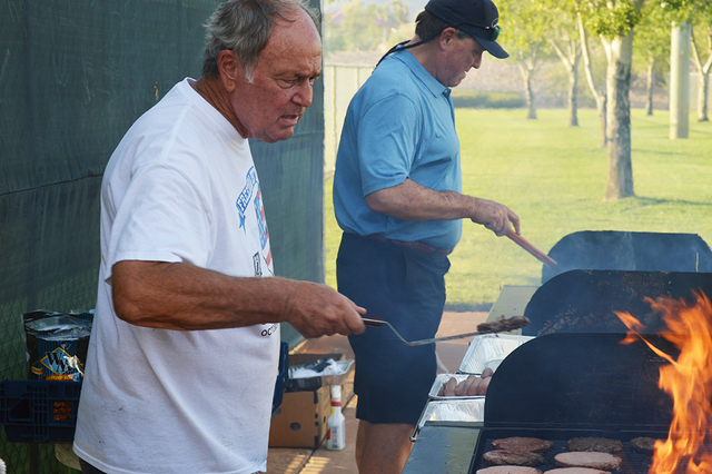 Jack Gaal cooks up burgers and hot dogs for those attending National Night Out on Tuesday at Veterans' Memorial Park. The owner of Jack's Place has been cooking at the event for the past three y ...