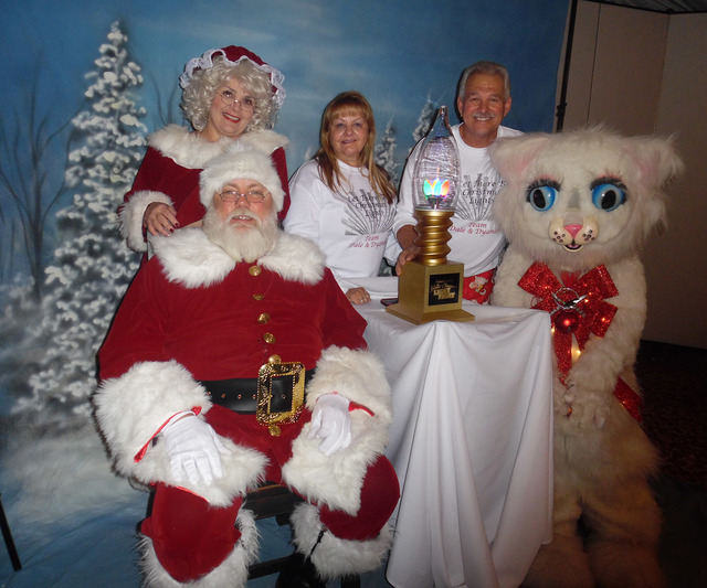 """Hali Bernstein Saylor/Boulder City Review Dyanah Musgrave and Dale Ryan join Santa and Mrs. Claus and Jingle Cat to show off the trophy they won competing in ABC's """"The Great Christmas Light Fight ..."""