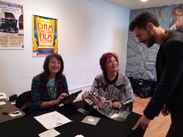 "Hali Bernstein Saylor/Boulder City Review Dam Short Film Festival volunteers Amanda Wolfe of Las Vegas, left, and Cici Dichello of Las Vegas, meet with Sam Blythe of London, producer of the film "" ..."