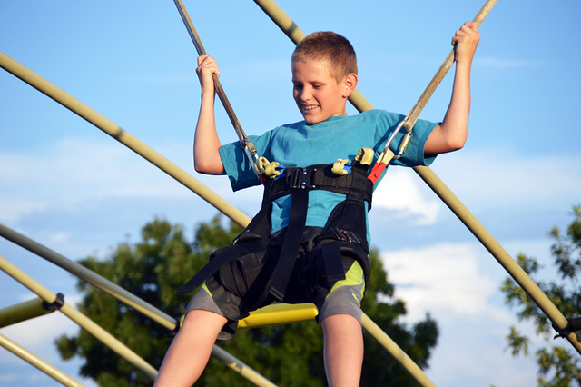 Joey Martin, 13, plays on the bungee jump during National Night Out on Tuesday at Veterans' Memorial Park while his mother Laurell Martin watches. Martin said it was important for her kids to inte ...