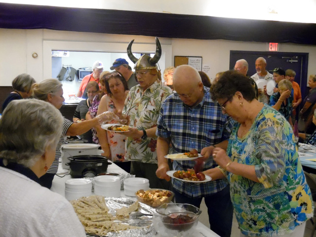 Hunter Terry/Boulder City Review Audrey and Leif Elstad, from right, Erik Elstad and Ida Hanson made it to the front of the line to fill their plates with fish, pork, Scandinavian meatballs and tr ...