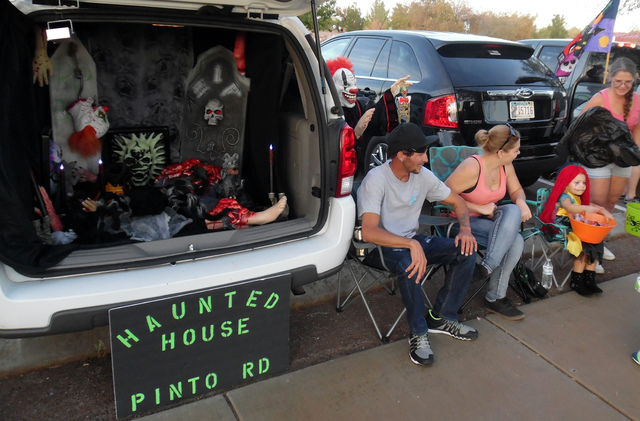 "Hunter Terry/Boulder City Review Jon Board and Leah Percy watch from the preview of their own haunted ""House of the Dam,"" as Lexi Board, 3, hands out candy at Trunk or Treat on Saturday at Veteran ..."