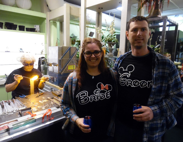 Hunter Terry/Boulder City Review Jennie Legrand and Craig Maxson of Las Vegas stopped at Boulder City Florist during the wine walk on Saturday and watched glass blowing by Dan Thompson, seated at  ...