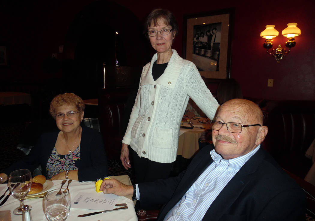 Hali Bernstein Saylor/Boulder City Review Rotary Club of Boulder City past president Lettie Zimmerman, standing, visits with Sharon and Gary Berger during the club's 80th anniversary celebration F ...