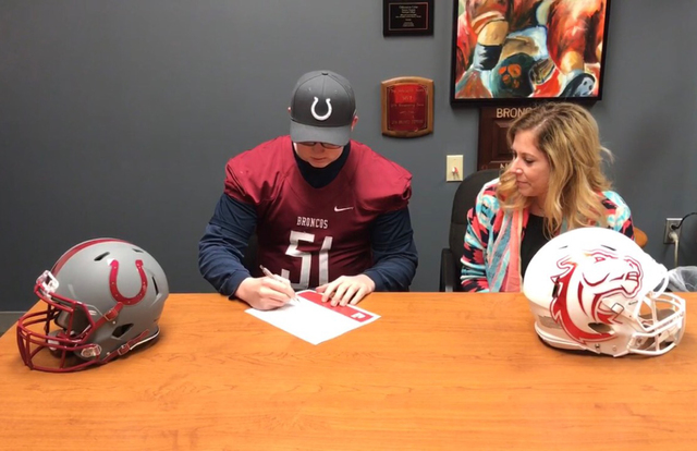 Photo courtesy Tony Harper Chase Cowley, a senior at Boulder City High School, has signed his national letter of intent to play football at Hastings College in Hastings, Nebraska. Looking on is hi ...
