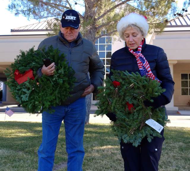 Hunter Terry/Boulder City Review Tom and Judy Barnes volunteered to lay wreaths at the grave of veterans Saturday at the Southern Nevada Veterans Memorial Cemetery as part of the Wreaths Across Am ...