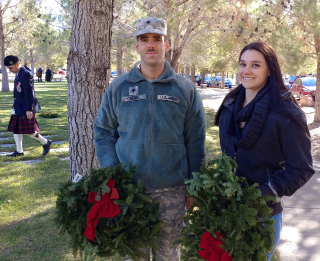 Hunter Terry/Boulder City Review U.S. Army Spcs. Balazs Bene, left, and Stephanie Michaels laid wreaths on graves Saturday at Southern Nevada Veterans Memorial Cemetery as part of Wreaths Across A ...