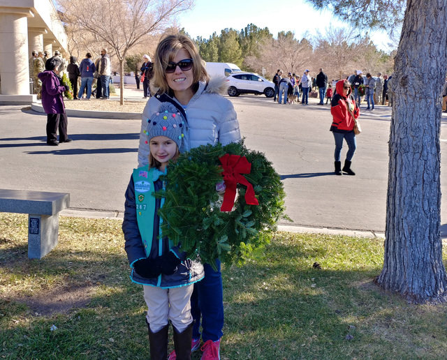 Hunter Terry/Boulder City Review Shannon and Grace Dickenson, in front, of Las Vegas, attended the Wreaths Across America ceremony Saturday at Southern Nevada Veterans Memorial Cemetery to pay the ...