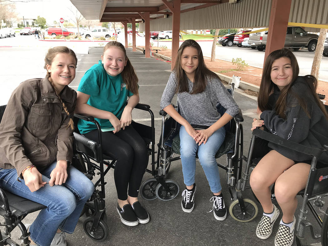 Hali Bernstein Saylor/Boulder City Review Taking shelter from the rain Saturday on the course for wheelchairs at the Rock, Roll & Stroll fundraiser for the Senior Center of Boulder City were, from ...