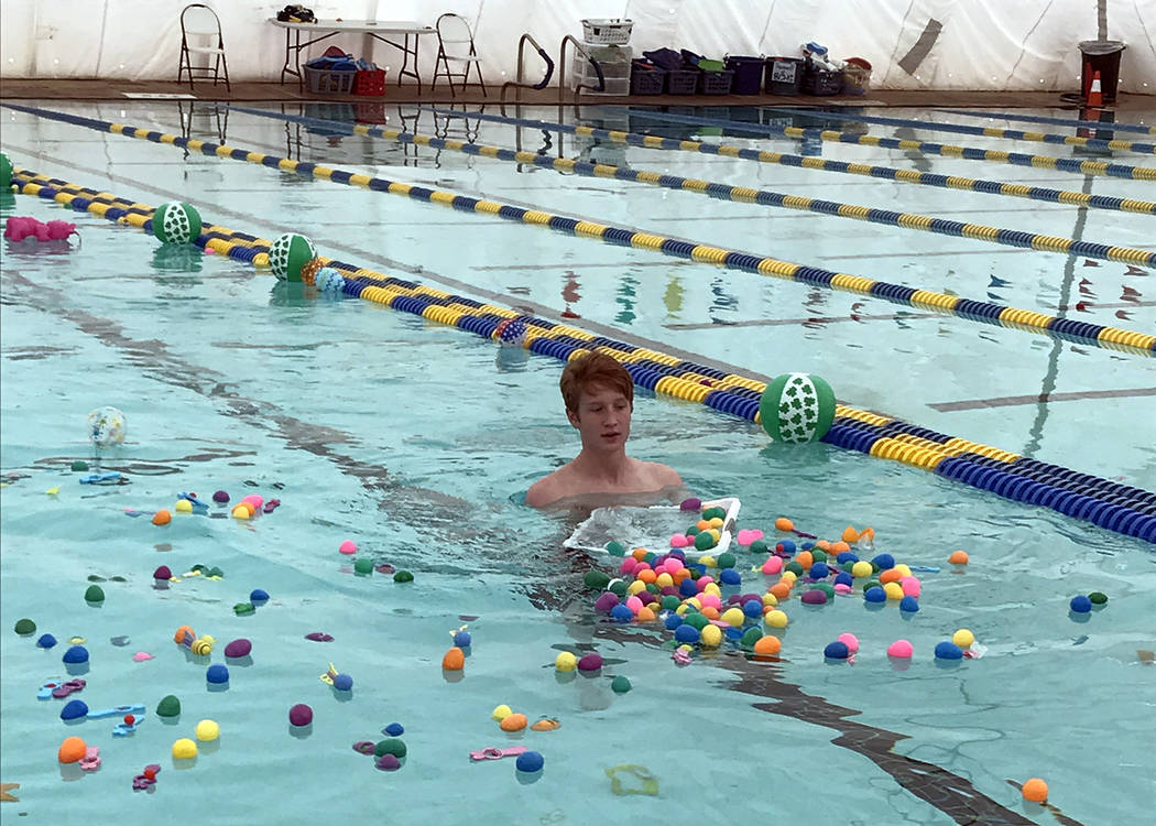 Hali Bernstein Saylor/Boulder City Review Lifeguard Tyson Morris helps spread plastic eggs in the municipal pool before the start of one of three egg hunts during the third annual Easter Pool Plun ...