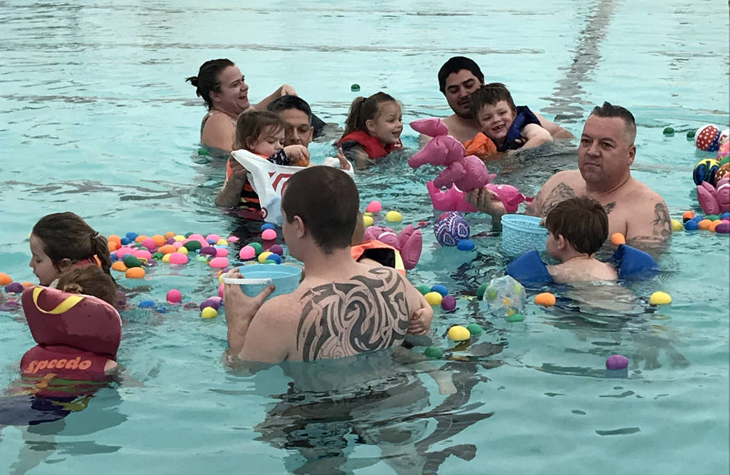 Hali Bernstein Saylor/Boulder City Review Children in the 0-5 age division, assisted by parents, gather plastic eggs and floating toys during the third annual Easter Pool Plunge on Saturday, March ...