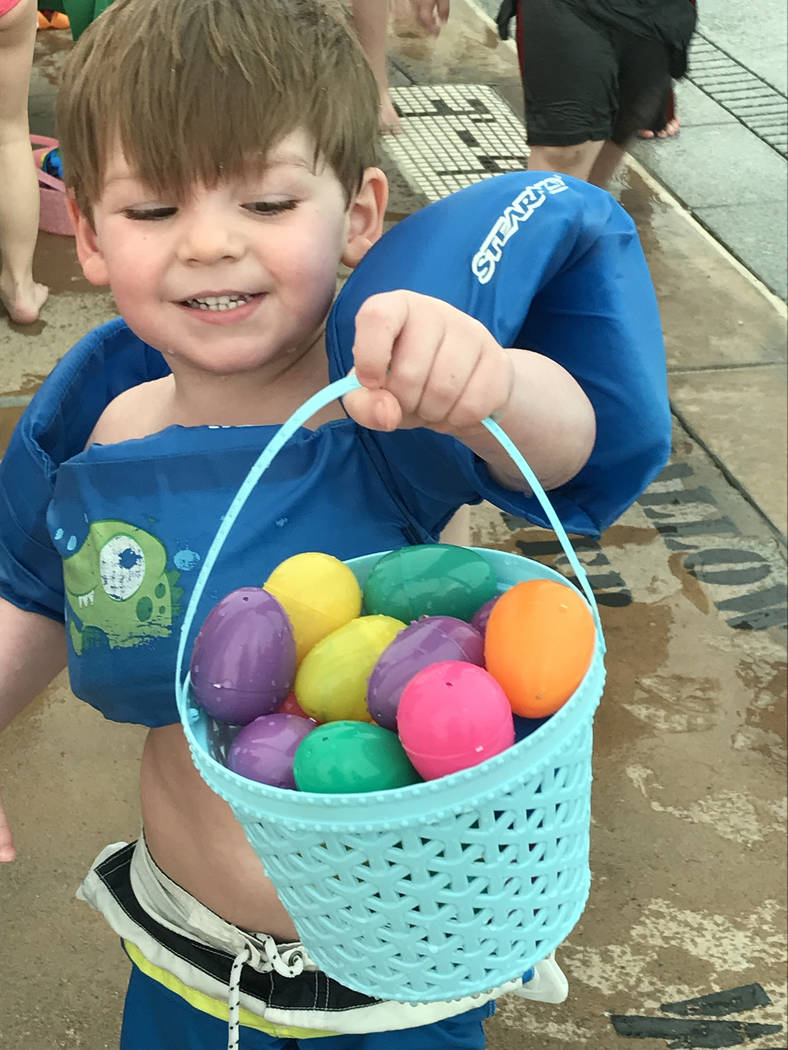 Hali Bernstein Saylor/Boulder City Review Braxden Cristo, 3, shows off the bucket of eggs he collected during the third annual Easter Pool Plunge on Saturday, March 17, 2018, at the municipal pool.