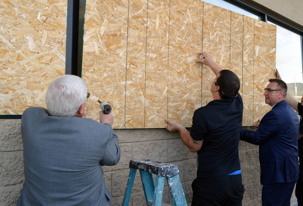 Celia Shortt Goodyear/Boulder City Review Councilman Kiernan McManus, left, helps Aaron Medo, center, and City Manager Al Noyola remove plywood from the old Vons/Haggen store on Boulder City Parkway.
