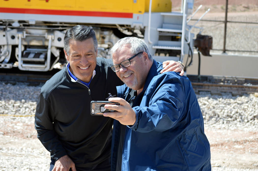 Celia Shortt Goodyear/Boulder City Review Guy Clifton, public relations specialist for Nevada Tourism and Cultural Affairs, snaps a selfie with Nevada Gov. Brian Sandoval at The Final Spike - A Hi ...