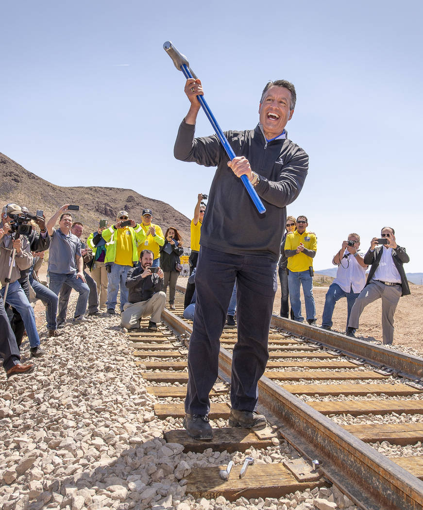 "Mark Damon/Las Vegas News Bureau Nevada Gov. Brian Sandoval hoists the hammer after driving the ""silver"" spike in the Final Spike ceremony as the Nevada State Railroad Museum in Boulder City celeb ..."