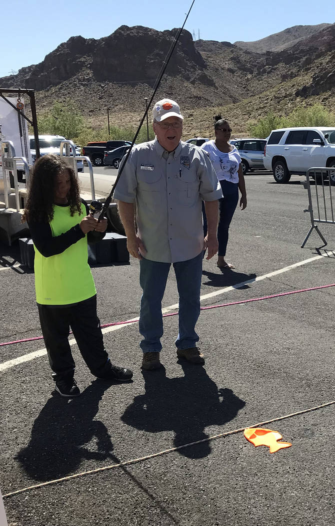 Hali Bernstein Saylor/Boulder City Review Eight-year-old Demetrius Wiest of Las Vegas gets a lesson on how to fish from Craig Schweisinger, a volunteer instructor for the Nevada Department of Wild ...