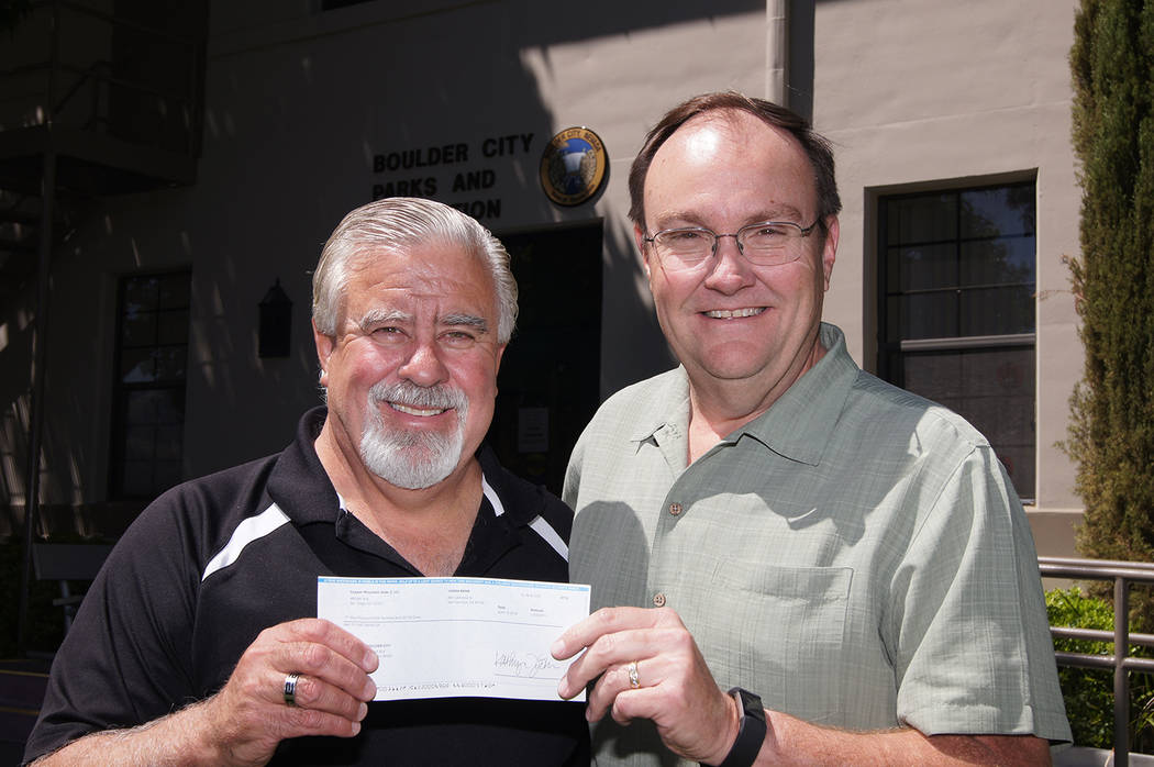 Boulder City Justin Hawkins, left, operations and maintenance manager for Copper Mountain Solar, Sempra Renewables, presents a $1,500 check to Roger Hall, Parks and Recreation director for Boulder ...