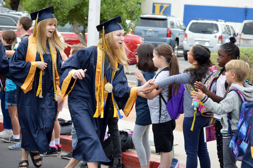 Celia Shortt Goodyear/Boulder City Review Boulder City High School senior Lauren Stewart, left, and valedictorian Camille Torgesen high-five students at King Elementary School during the fourth an ...