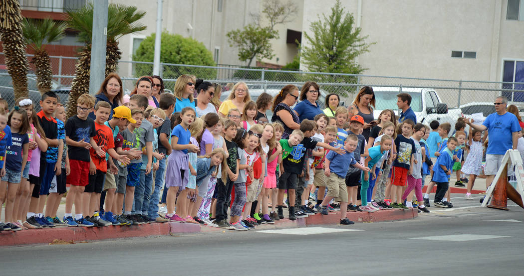 Celia Shortt Goodyear/Boulder City Review Elementary school students wait for their turn to high-five members of Boulder City High School's class of 2018 during the Grad Walk on Monday, May 21. Th ...