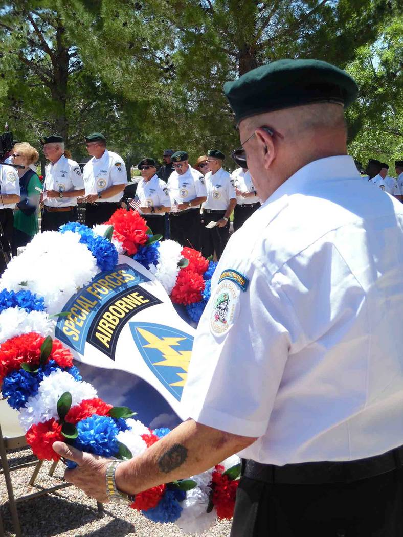 File A member of the Special Forces Association, Chapter 51, prepares to lay a floral wreath during Memorial Day ceremonies in 2017 at the Southern Nevada Veterans Memorial Cemetery. This year's c ...