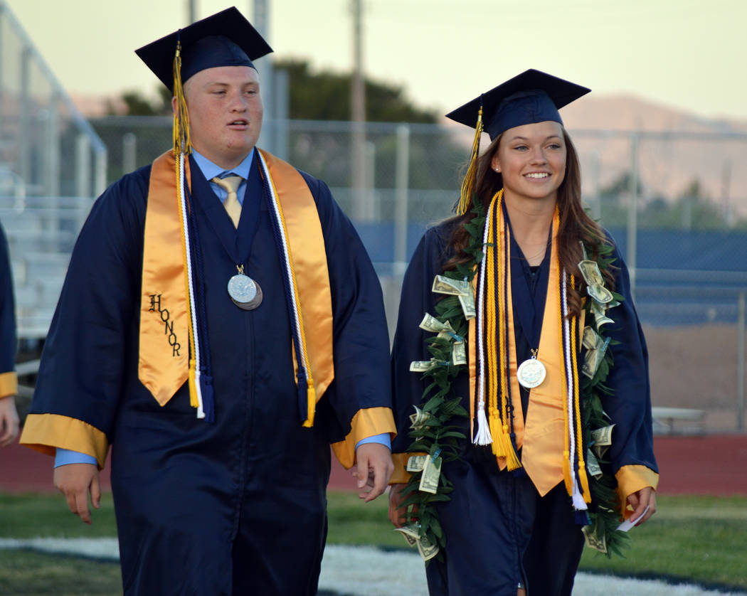 Celia Shortt Goodyear/Boulder City Review Graduating seniors Nolan Herr and Lani Potter walk onto Bruce Eaton Field on Friday for the school's 77th commencement.
