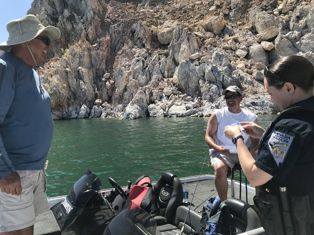 Hali Bernstein Saylor/Boulder City Review Brittany Frolick, a game warden with the Nevada Department of Wildlife, checks the fishing licenses of Keith Hoffman of Boulder City, left, and Matt Hoffm ...