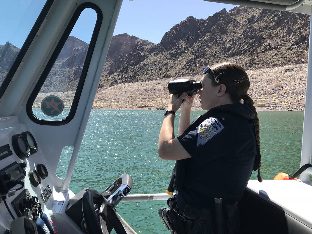 Hali Bernstein Saylor/Boulder City Review Nevada Department of Wildlife game warden Brittany Frolick uses binoculars to ensure that a nearby boat and water skiers are following safety regulations ...