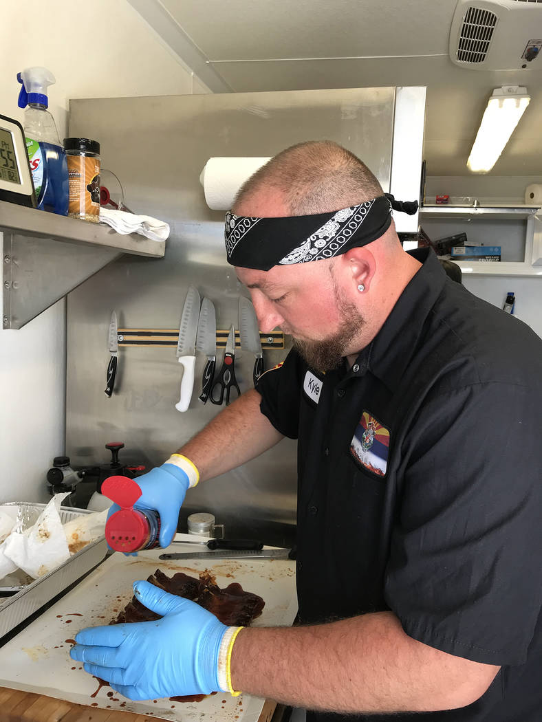 Hali Bernstein Saylor/Boulder City Review Kyle Matuszewski of Your Behind BBQ of Waddell, Arizona, puts finishing touches on his ribs before turning them into to judges on Saturday, May 26, 2018, ...