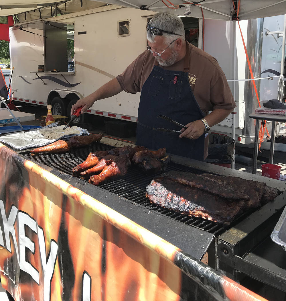 Hali Bernstein Saylor/Boulder City Review Rick Eide of Great Basin Barbecue serves up turkey legs and slabs of ribs on Saturday, May 26, 2018, at the Best Dam Barbecue Challenge presented by the R ...