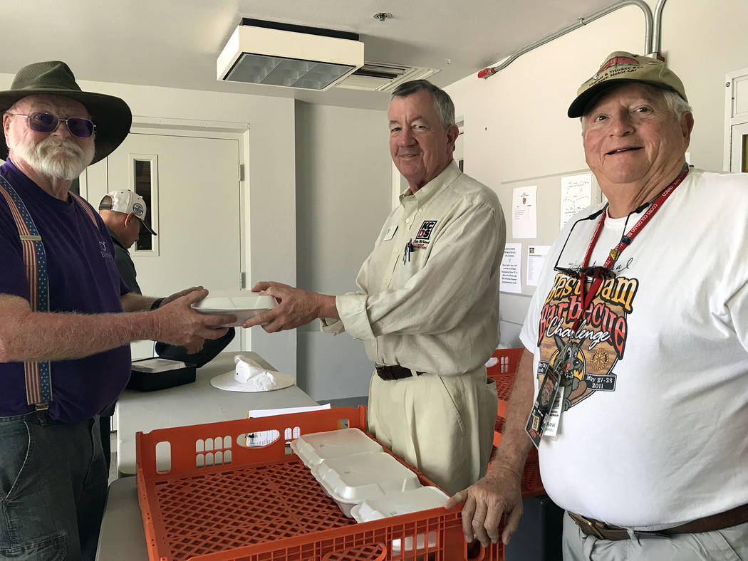 Hali Bernstein Saylor/Boulder City Review Mike Verner, left, of Infinite Smoke, turns in his brisket entry to Kelly MacIntosh of the Kansas City Barbeque Society, center, and Frank Carroll of the ...