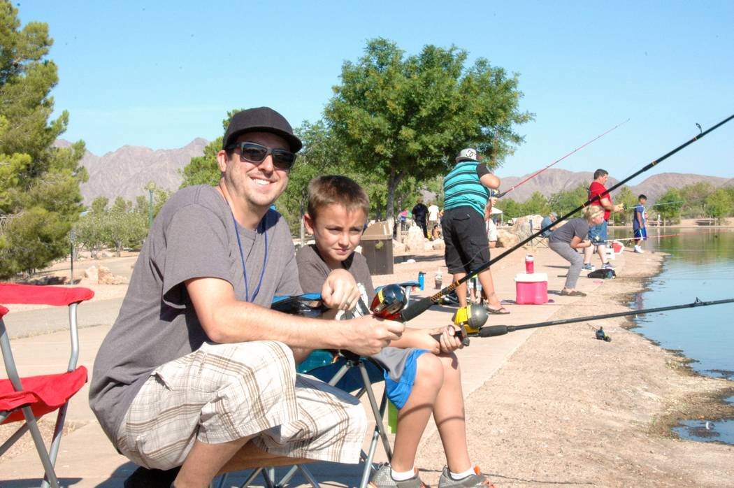 Jayme Sileo/Boulder City Review Anthony McLeod and his son Keagan McLeod wait to get their first bite out of Veterans' Memorial Park's fishing pond during Free Fishing Day on Saturday.