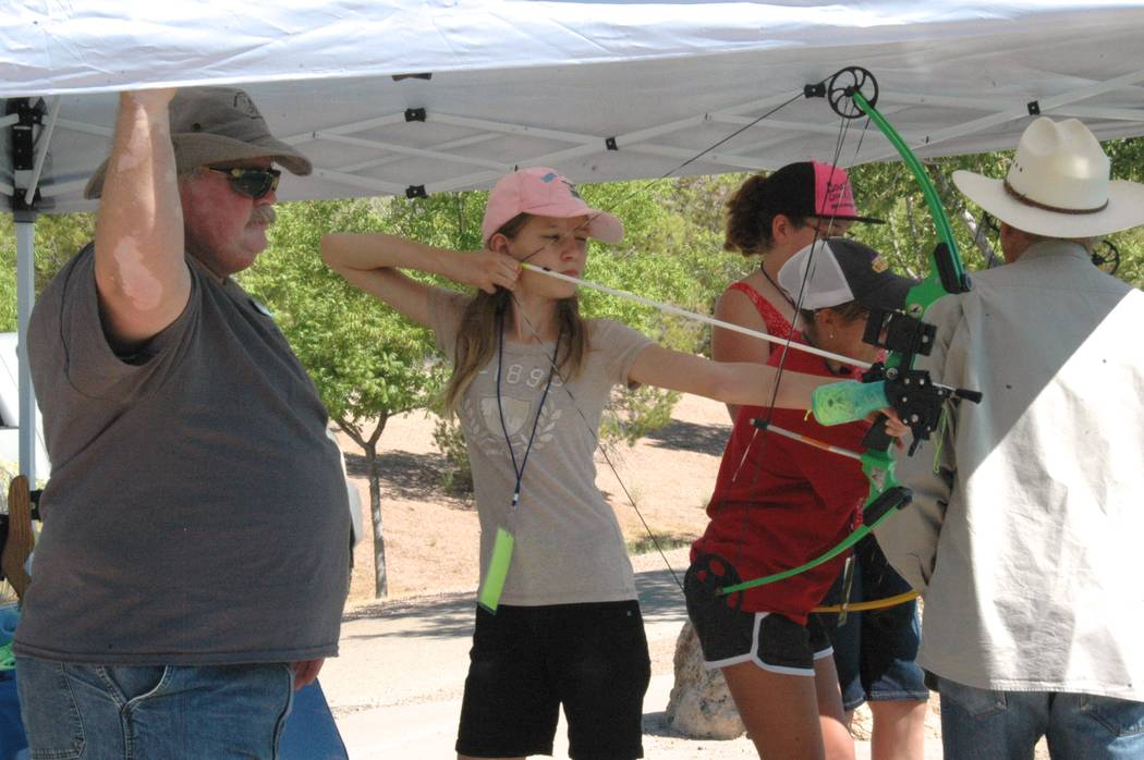 Jayme Sileo/Boulder City Review Nevada Department of Wildlife volunteer William Bly helped staff the bowfishing activity tent where Annalise Johnson and others practiced shooting fake fish with a ...