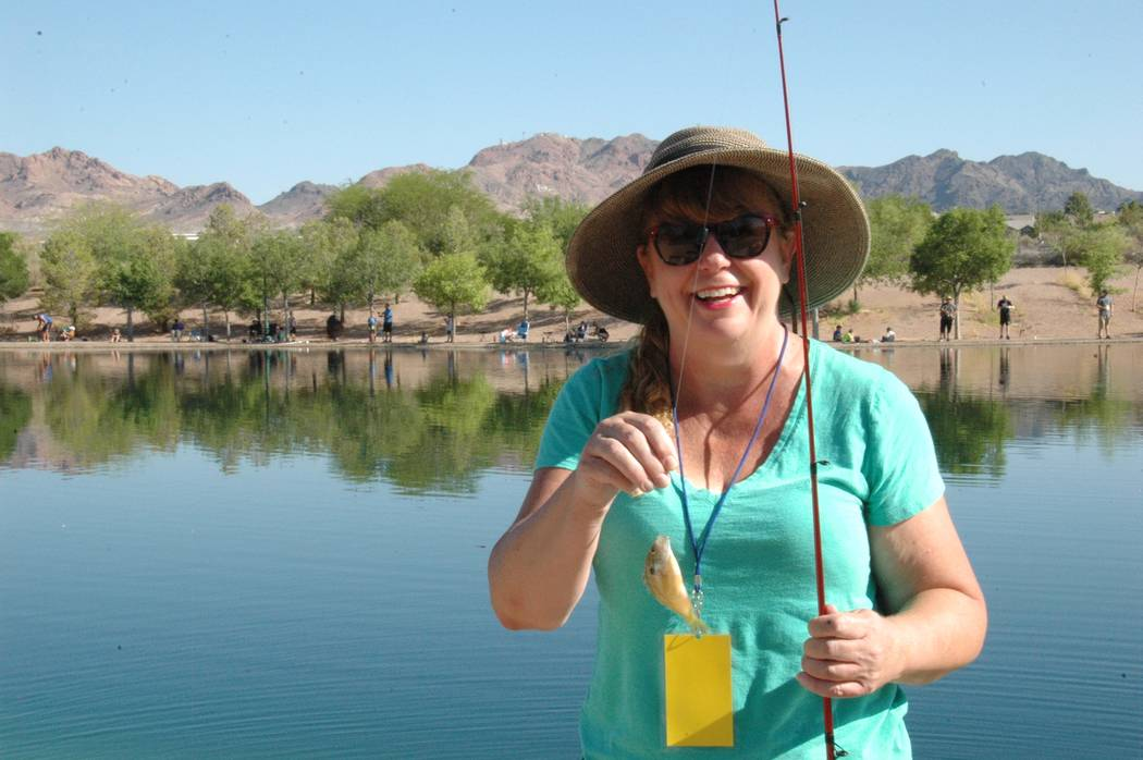 Jayme Sileo/Boulder City Review Debbie Finkel shows off her first catch of the day on Saturday during Free Fishing Day at Veterans' Memorial Park.