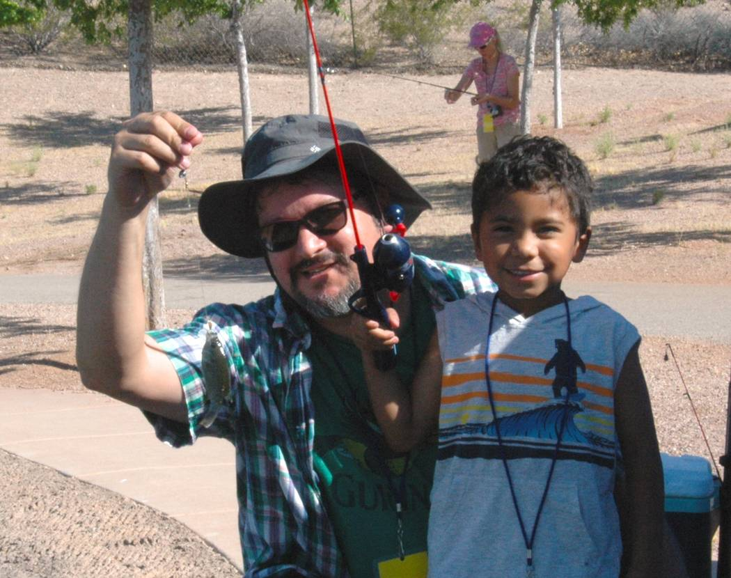 Jayme Sileo/Boulder City Review Jesse Espinoza, 4, caught his first fish all by himself during Free Fishing Day on Saturday. Andy Espinoza holds up the prized fish.