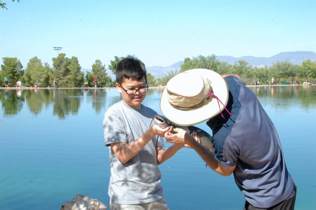 Jayme Sileo/Boulder City Review McKinley Baker's second fish of the day during Free Fishing Day activities at Veterans' Memorial Park was a 20-inch catfish; Francis Baker is seen helping detach th ...