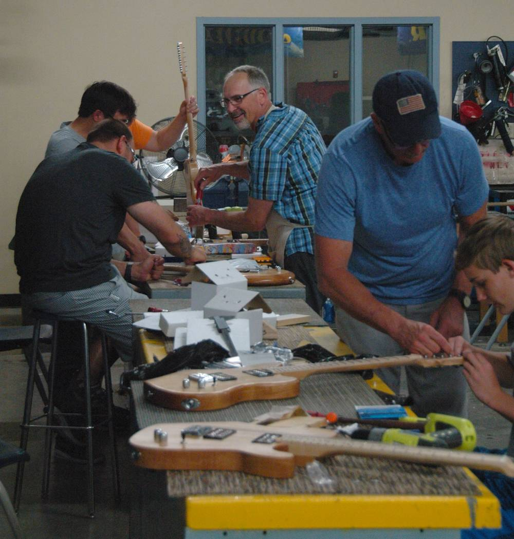 Jayme Sileo/Boulder City Review STEM Guitar summer institute instructor Mike Aikens, second from right, helps Jake Trone, far right, with his electric guitar while Steve Brown, center, guides teac ...