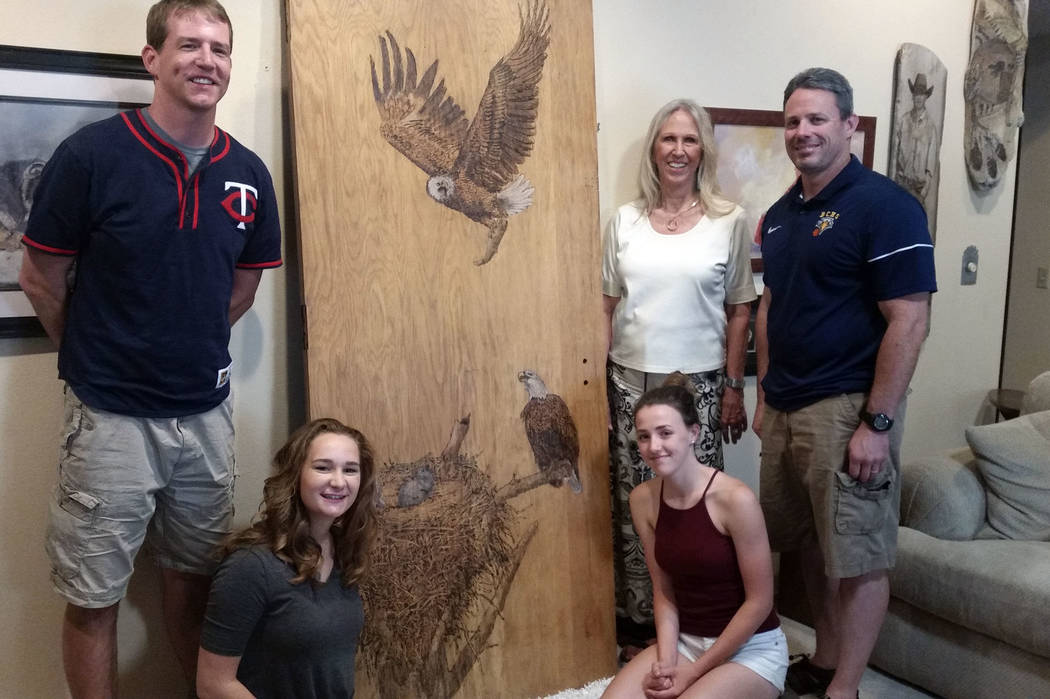 Celia Shortt Goodyear/Boulder City Review Boulder City artist Lynne Jordan, second from right, showcases a new pyrographic sculpture she made from a door Canaan Petersen, left, salvaged from the o ...