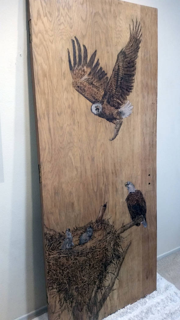 "Celia Shortt Goodyear/Boulder City Review Boulder City artist Lynne Jordan created a pyrographic sculpture, ""From Eaglets to Eagles,"" from a repurposed door from an old Boulder City High School bu ..."