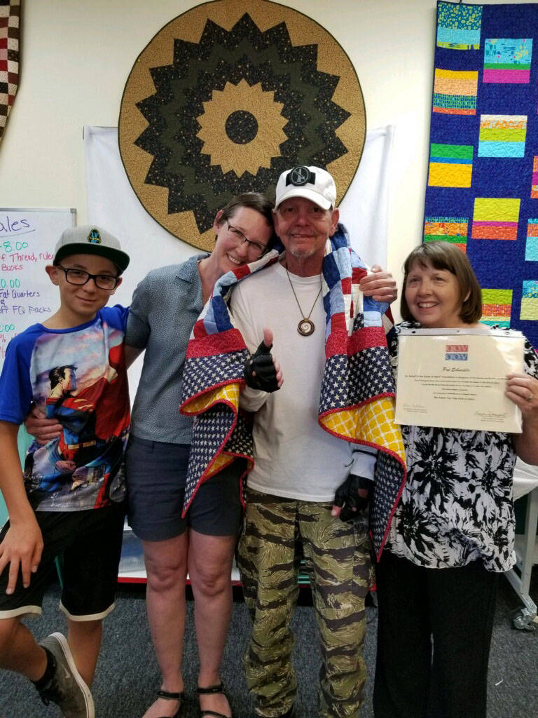 Patrick Schneider Patrick Schneider, second from right, received his award from the Quilts of Valor Foundation on Sunday, June 24, 2018, from Royce Gansert, from left, Stacy Norman and Lora Norman ...
