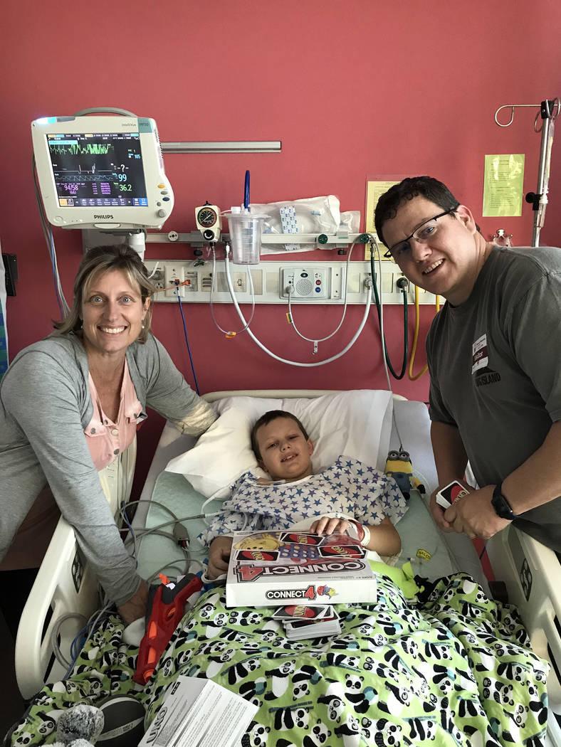 Tara Bertoli T.J. Bertoli, center, plays a game with his parents, Tara and Troy Bertoli after having surgery to fix damage to his left hip from Legg-Calve-Perthes disease.