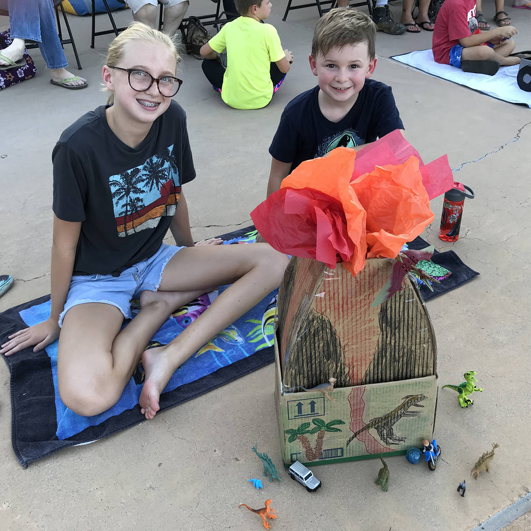 Hali Bernstein Saylor/Boulder City Review Andrew Hyusentruyt, 7, entered The Volcano into the 18th annual cardboard boat races at Boulder City Pool on July 25. Joining him for the fun was his sist ...