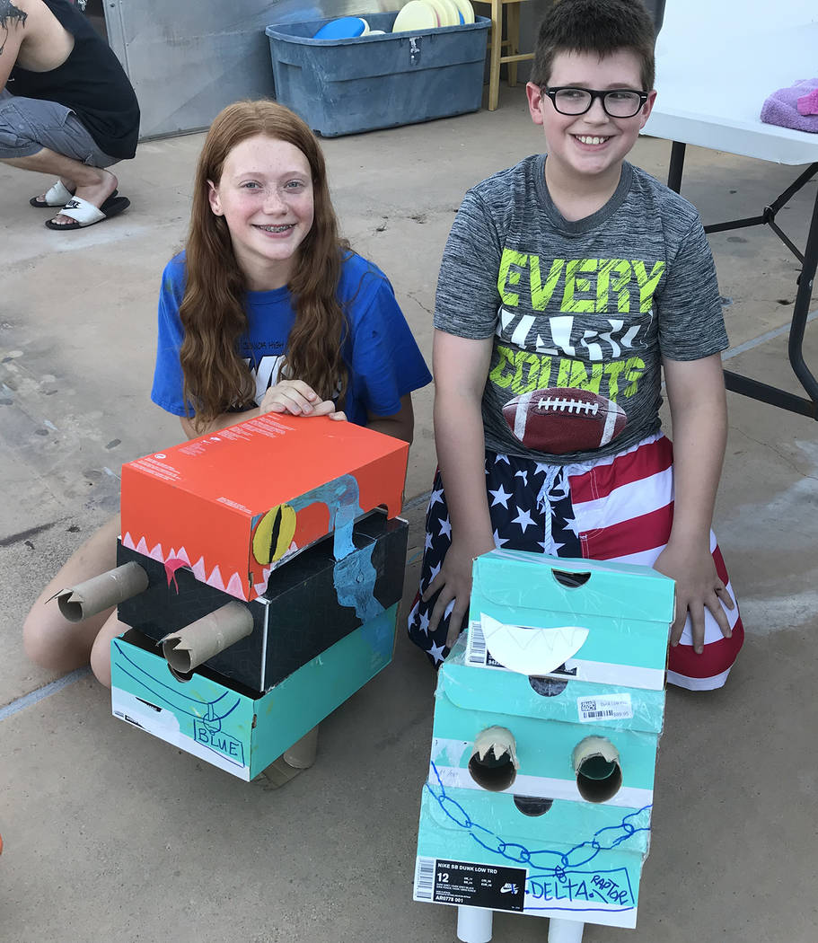 Hali Bernstein Saylor/Boulder City Review Morgan Barrow, 13, and Logan Barrow, 10, created their versions of velociraptors Blue and Delta, respectively, for the 18th annual cardboard boat races at ...