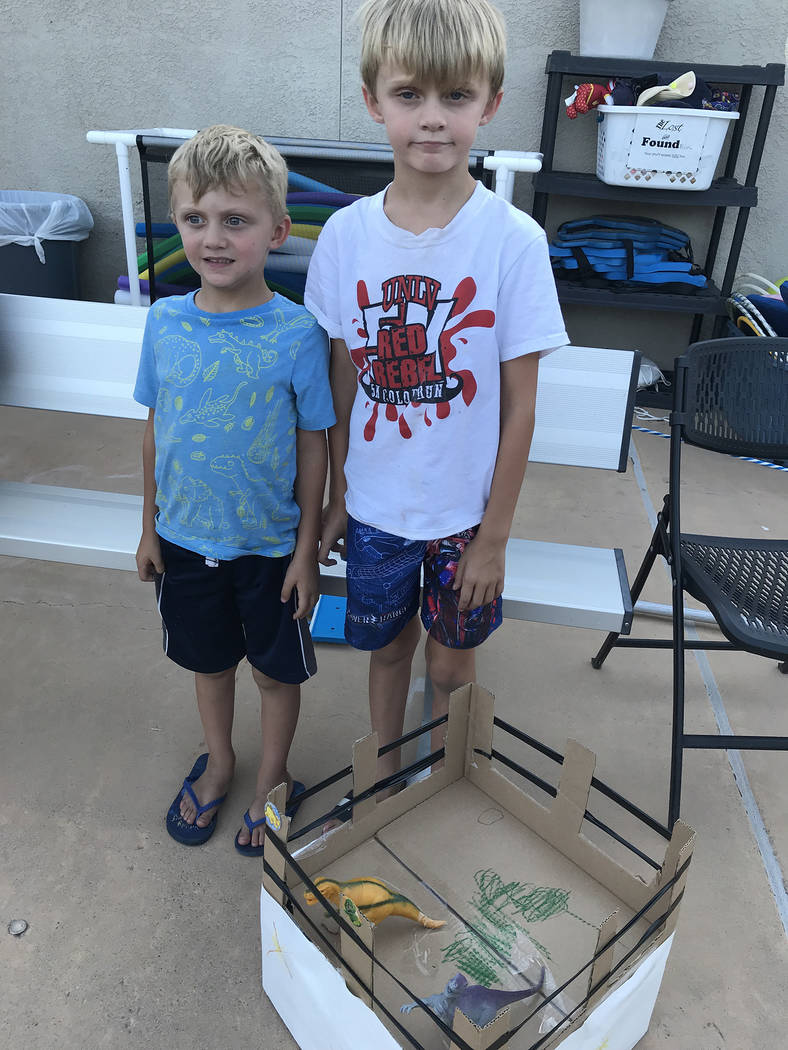 Hali Bernstein Saylor/Boulder City Review Brothers Quinlan, 5, and Brendan Smith, 8, presented the Dino Cave for the 18th annual cardboard boat races on July 25.