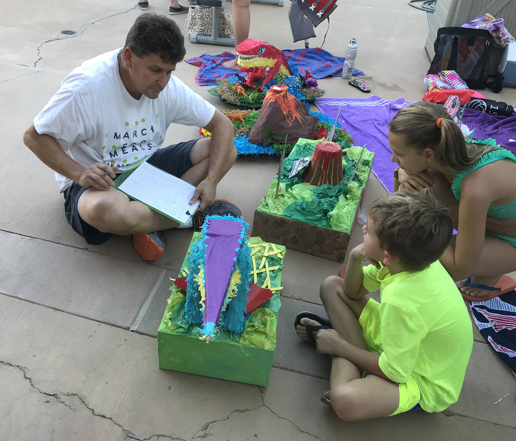 Hali Bernstein Saylor/Boulder City Review Mayor Rod Woodbury talks to Michael and Makenzie Martorano about their entries while judging the 18th annual cardboard boat races at the Boulder City Pool ...