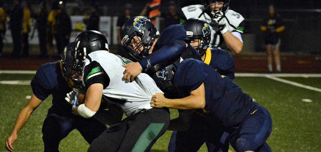 Robert Vendettoli/Boulder City Review Nick Schellenberg, a sophomore at Boulder City High School, leads a group of gang tacklers against Virgin Valley running back Wyatt Delano on Sept. 20. The Ea ...