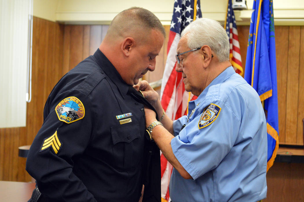 Celia Shortt Goodyear/Boulder City Review Retired New York City Police officer George Tomao pins a badge on his son, Craig Tomao, after he was sworn in at City Hall on Monday, Oct. 1, as one of tw ...